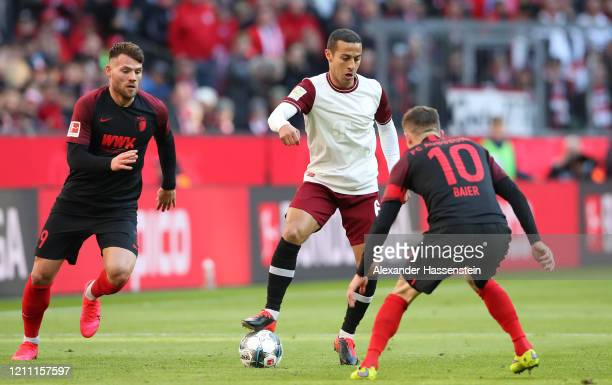 Thiago Alcantara of Bayern Munich battles for possession with Eduard Lowen of Augsburg and Daniel Baier of Augsburg during the Bundesliga match...