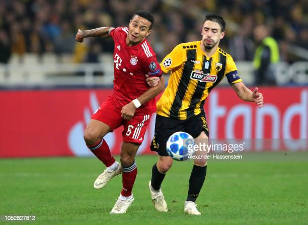 Thiago Alcantara of Bayern Munich challenges for the ball with Andre Simoes of AEK Athens during the Group E match of the UEFA Champions League...