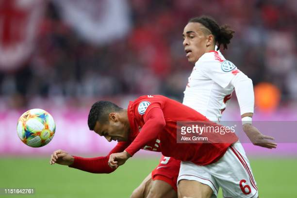 Thiago Alcantara of Bayern Munich clears from Yussuf Poulsen of RB Leipzig during the DFB Cup final between RB Leipzig and Bayern Muenchen at...