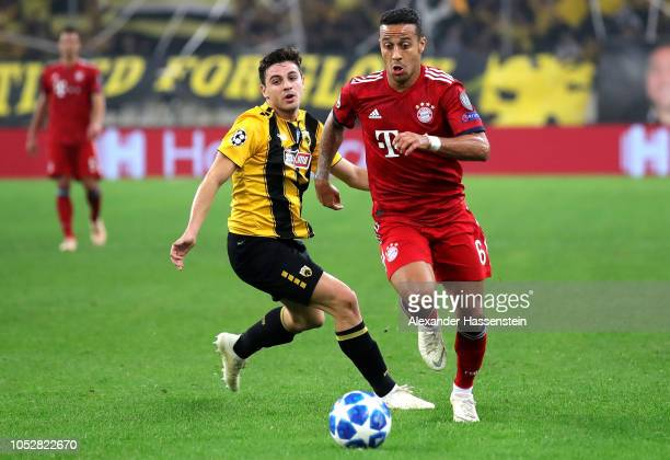 Thiago Alcantara of Bayern Munich is challenged by Kostas Galanopoulos of AEK Athens during the Group E match of the UEFA Champions League between...