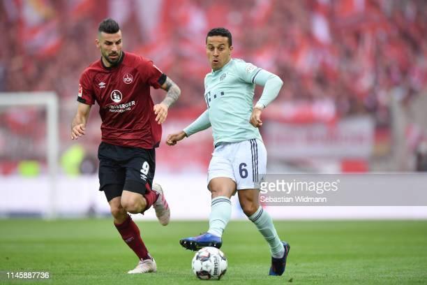 Thiago Alcantara of Bayern Munich plays the ball as Mikael Ishak of Nuernberg runs next to him during the Bundesliga match between 1. FC Nuernberg...