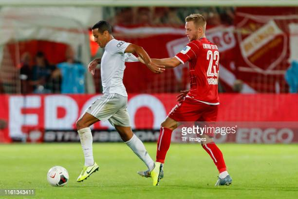 Thiago Alcantara of FC Bayern Muenchen and Felix Bruegmann of Energie Cottbus battle for the ball during the DFB Cup first round match between...