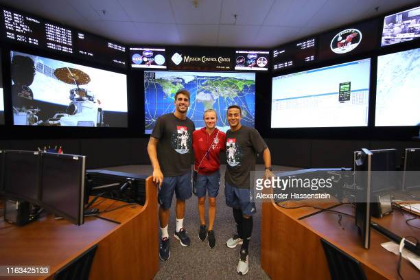 Thiago Alcantara of FC Bayern Muenchen and team mate Javier Martinez poses with team manger Kathleen Krueger as they visit the Nasa Mission Control...
