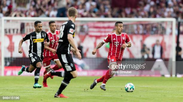 Thiago Alcantara of FC Bayern Muenchen is challenged by Matthias Ginter of Borussia Moenchengladbach and Raffael of Borussia Moenchengladbach during...