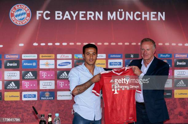 Thiago Alcantara of FC Bayern Muenchen presents his new match jersey with FCB managing director KarlHeinz Rummenigge after a press conference at...