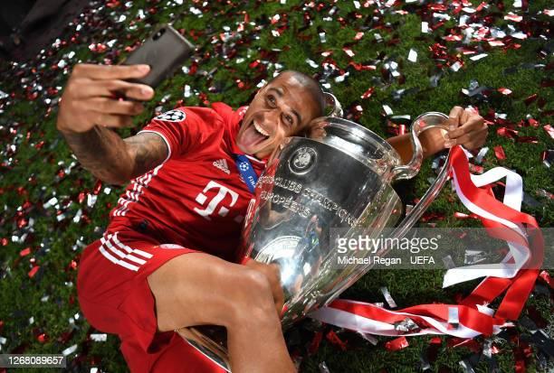 Thiago Alcantara of FC Bayern Munich celebrates with the UEFA Champions League Trophy following his team's victory in the UEFA Champions League Final...