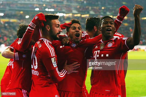 Thiago Alcantara of Muenchen celebrates his team's second goal with team mates Diego Contento and David Alaba during the Bundesliga match between VfB...
