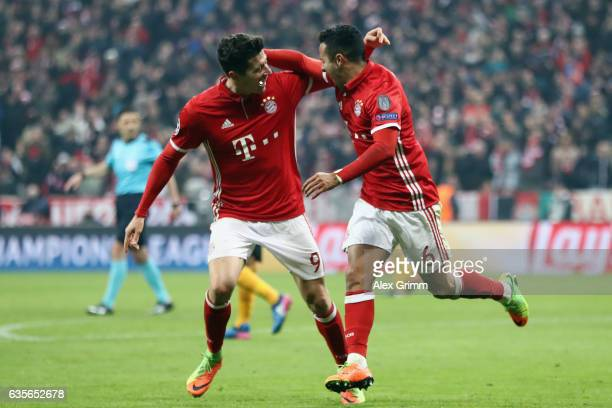 Thiago Alcantara of Muenchen celebrates his team's third goal with team mate Robert Lewandowski during the UEFA Champions League Round of 16 first...