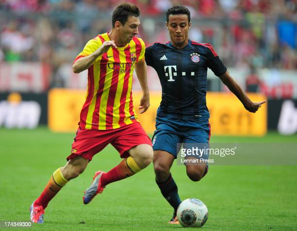 Thiago Alcantara of Muenchen challenges Lionel Messi of Barcelona during the Uli Hoeness Cup match between FC Bayern Muenchen and FC Barcelona at...