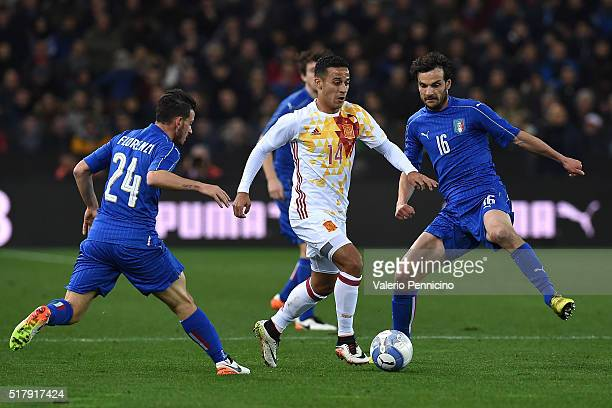 Thiago Alcantara of Spain in action against Marco Parolo and Alessandro Florenzi of Italy during the international friendly match between Italy and...