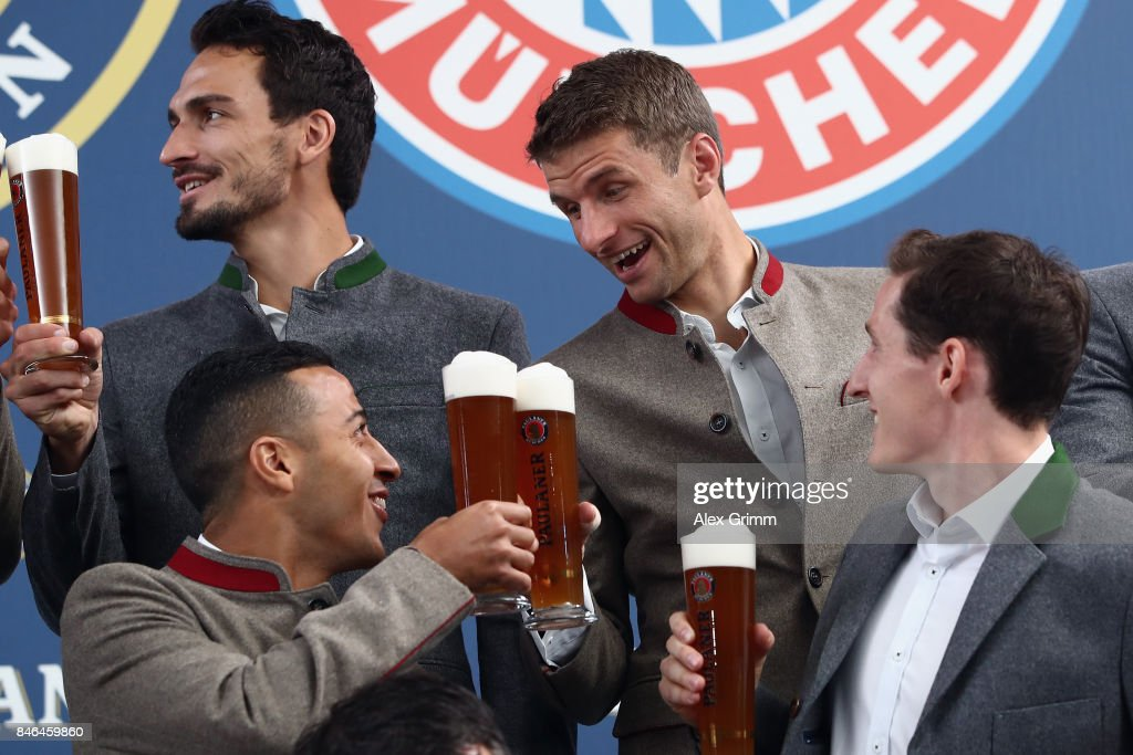 Thiago Alcantara raises a birthday toast to Thomas Mueller during the FC Bayern Muenchen Paulaner photo shoot in traditional Bavarian lederhosen on September 13, 2017 in Munich, Germany.
