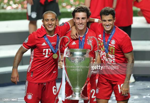 Thiago Alvaro Odriozola and Philippe Coutinho of FC Bayern Munich celebrate with the UEFA Champions League Trophy following their team's victory in...