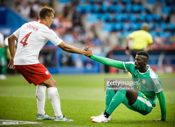 Thiago Cionek of Poland gives Mbaye Niang of Senegal a hand during the 2018 FIFA World Cup Russia group H match between Poland and Senegal at Spartak...
