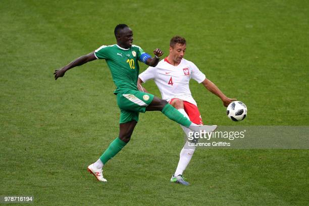 Thiago Cionek of Poland is tackled by Sadio Mane of Senegal during the 2018 FIFA World Cup Russia group H match between Poland and Senegal at Spartak...