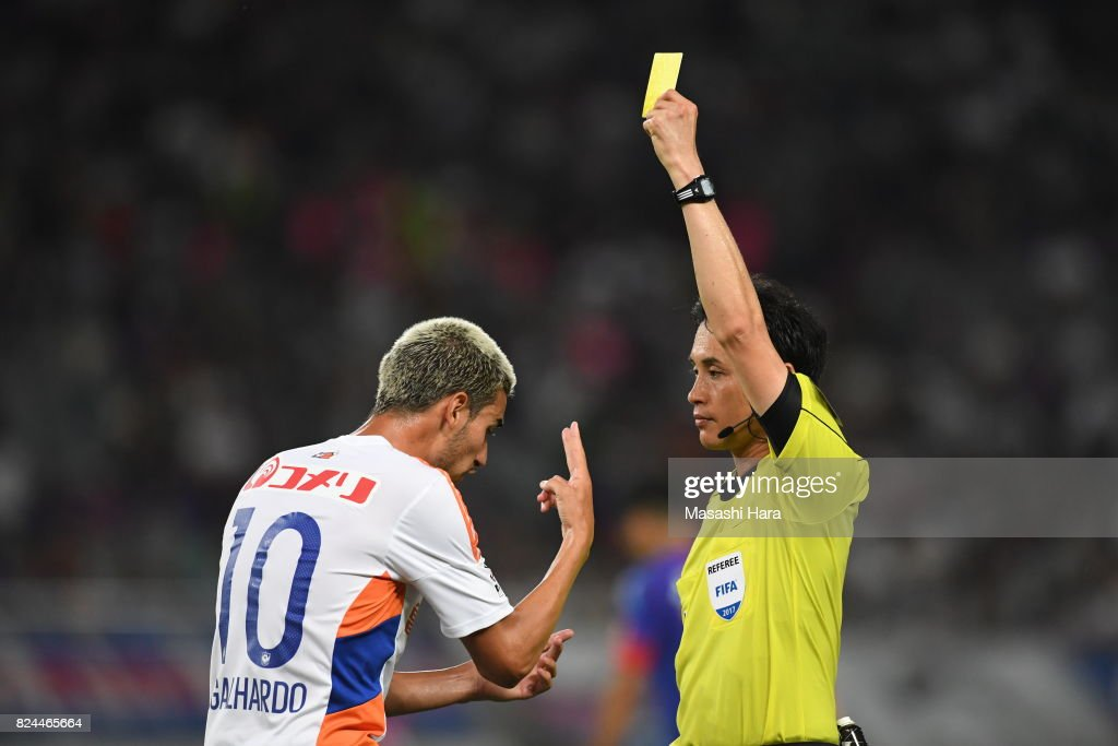 Thiago Galhardo do Nascimento Rocha (L) of Albirex Niigata is shown a yellow card by referee Hiroyuki Kimura during the J.League J1 match between FC Tokyo and Albirex Niigata at Ajinomoto Stadium on July 30, 2017 in Chofu, Tokyo, Japan.