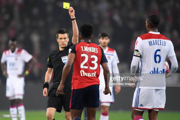 Thiago Henrique Mendes Riberio of Lille receives a yellow card from referee Benoit Bastien during the French League 1 match between Lille v Olympique...