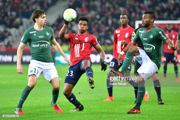 Thiago Mendes of Lille tries to slip between Ole Selnaes of St Etienne and Habib Maiga of St Etienne during the Ligue 1 match between Lille OSC and...