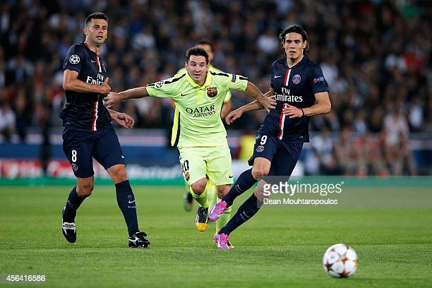 Thiago Motta and Edinson Cavani of PSG stop the attack from Lionel Messi of Barcelona during the Group F UEFA Champions League match between Paris...