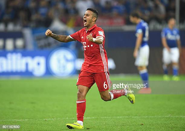 Thiago of Bayern Muenchen celebrates after Robert Lewandowski scores his sides first goal during the Bundesliga match between FC Schalke 04 and...