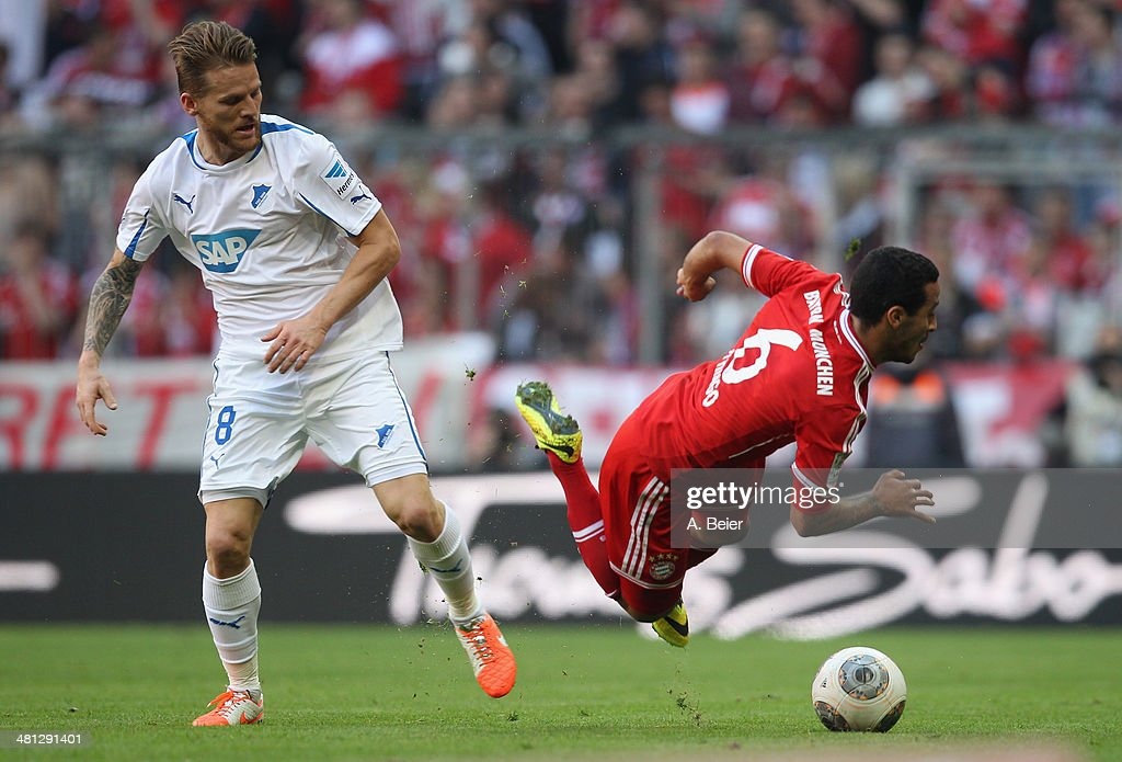 Thiago (R) of Bayern Muenchen is tackled by Eugen Polanski of Hoffenheim during the Bundesliga match between FC Bayern Muenchen and 1899 Hoffenheim at Allianz Arena on March 29, 2014 in Munich, Germany.