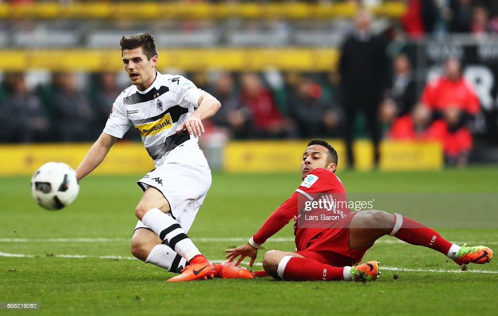 Thiago of Bayern Munich challenges Jonas Hofmann of Borussia Moenchengladbach during the Bundesliga match between Borussia Moenchengladbach and Bayern Muenchen at Borussia-Park on March 19, 2017 in Moenchengladbach, Germany.