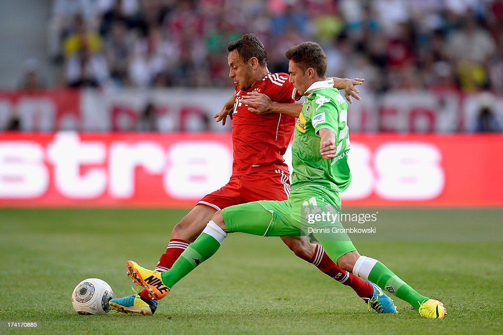 Thiago of FC Bayern Muenchen is challenged by Branimir Hrgota of Borussia Moenchengladbach during the Telekom 2013 Cup final between FC Bayern Muenchen and Borussia Moenchengladbach on July 21, 2013 in Moenchengladbach, Germany.