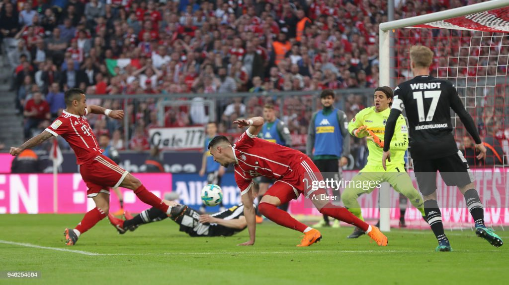 Thiago (L) of FC Bayern Muenchen scores his first goal against goalkeeper Yann Sommer (2ndR) of Moenchengladbach during the Bundesliga match between FC Bayern Muenchen and Borussia Moenchengladbach at Allianz Arena on April 14, 2018 in Munich, Germany.