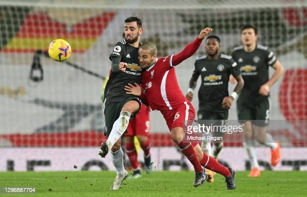 Thiago of Liverpool challenges for the ball with Bruno Fernandes of Manchester United during the Premier League match between Liverpool and...