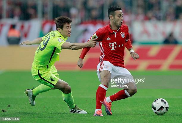 Thiago of Muenchen and Ja Cheol Koo of Augsburg battle for the ball during the DFB Cup second round match between Bayern Muenchen and FC Augsburg at...