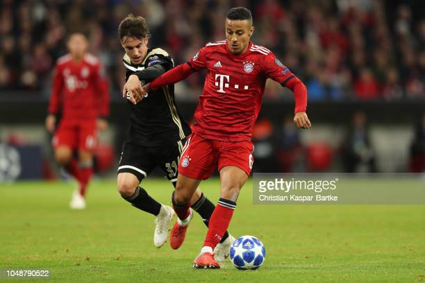 Thiago of Muenchen challenges Nicolas Tagliafico of Amsterdam during the Group E match of the UEFA Champions League between FC Bayern Muenchen and...