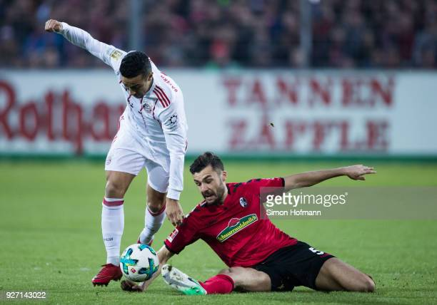 Thiago of Muenchen is challenged by Manuel Gulde of Freiburg during the Bundesliga match between SportClub Freiburg and FC Bayern Muenchen at...