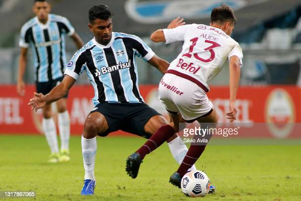 Thiago Santos of Gremio competes for the ball with Julian Aude of Lanus during a match between Gremio and Lanus as part of group H of Copa CONMEBOL...