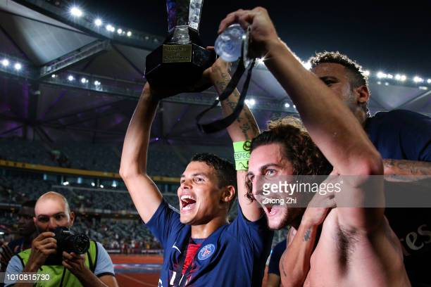 Thiago Silva Adrien Rabiot and Neymar of Paris SaintGermain celebrate with trophy after winning the French Trophy of Champions football match between...