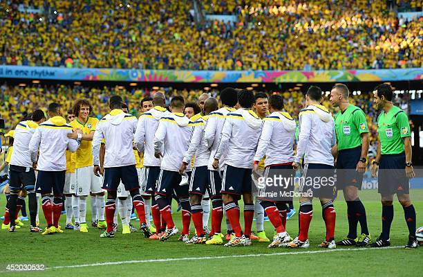 Thiago Silva and David Luiz of Brazil shake hands with the Colombia players prior to the 2014 FIFA World Cup Brazil Quarter Final match between...