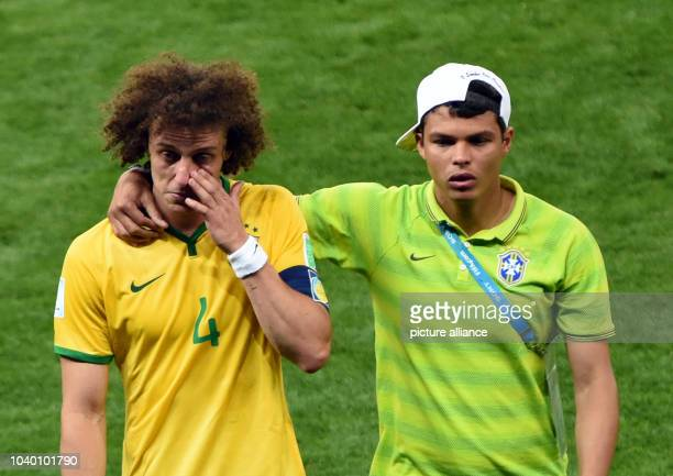 Thiago Silva of Brazil and David Luiz react after the FIFA World Cup 2014 semi-final soccer match between Brazil and Germany at Estadio Mineirao in...
