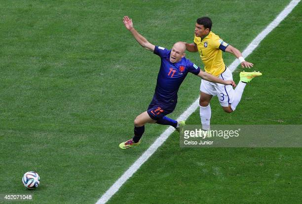 Thiago Silva of Brazil challenges Arjen Robben of the Netherlands resulting in a penalty kick for the Netherlands and yellow card for Silva during...