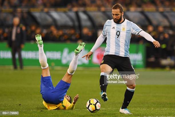 Thiago Silva of Brazil falls over as Gonzalo Higuain of Argentina competes for the ball during the Brasil Global Tour match between Brazil and...