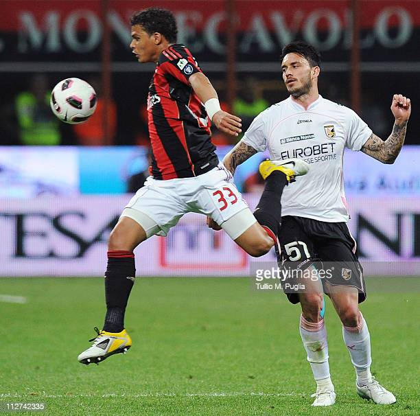 Thiago Silva of Milan jumps for the ball as Mauricio Pinilla of Palermo tackles during the TIM Cup semifinal match between AC Milan and US Citta di...