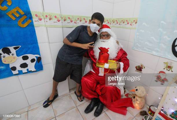 Thiago Venancio poses with Santa Claus at the Christmas party at Uniao de Mulheres Pro Melhoramentos da Roupa Suja Kindergarten in Favela da Rocinha...