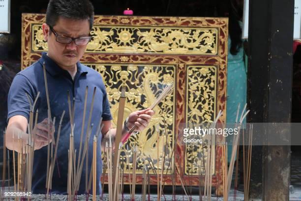 Thian Hock Keng Temple A Chinese man praying and offering incense Buddhist Worshipper Burning incense sticks Singapore