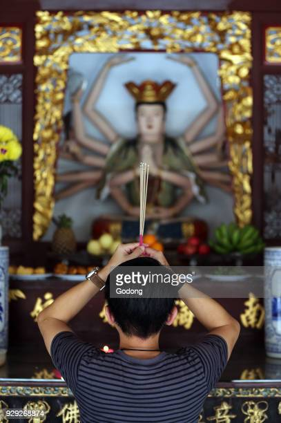 Thian Hock Keng Temple A Chinese young man praying and offering incense Buddhist Worshipper Burning incense sticks Man praying Singapore