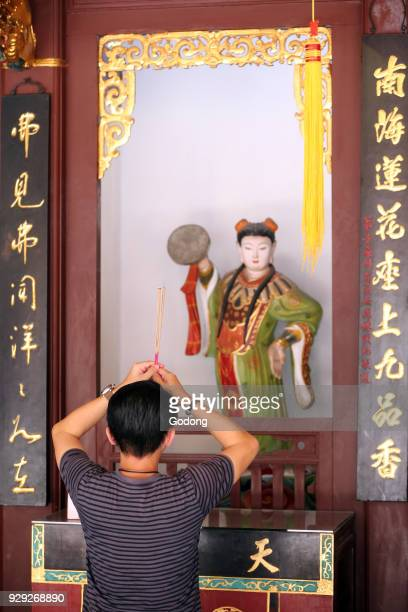 Thian Hock Keng Temple A Chinese young man praying and offering incense Buddhist Worshipper Burning incense sticks Yue Gong Niang Niang the moon...