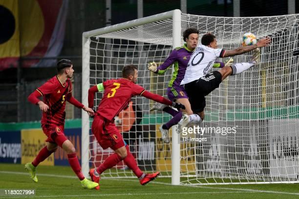 Thibault De Smet of Belgium Zinho Vanheusden of Belgium goalkeeper Mile Svilar of Belgium and Lukas Nmecha of Germany battle for the ball during the...