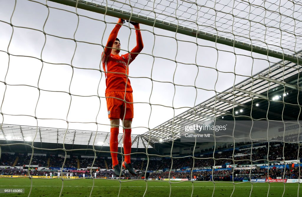 Thibaut Courtois jumps up to the crossbar during the Premier League match between Swansea City and Chelsea at Liberty Stadium on April 28, 2018 in Swansea, Wales.