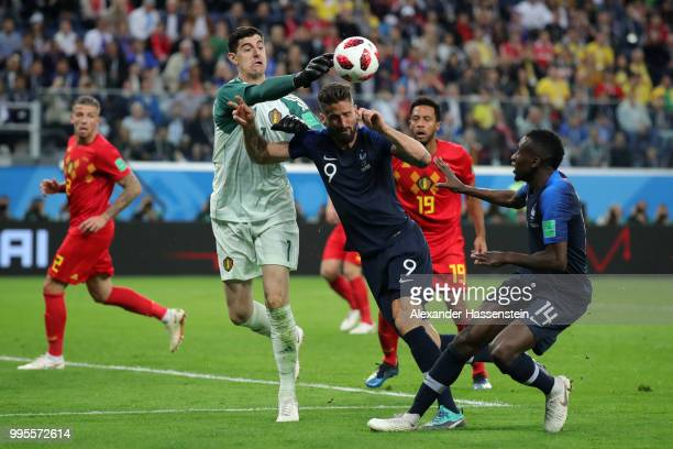 Thibaut Courtois of Belgium clears the ball under pressure from Olivier Giroud of France during the 2018 FIFA World Cup Russia Semi Final match...