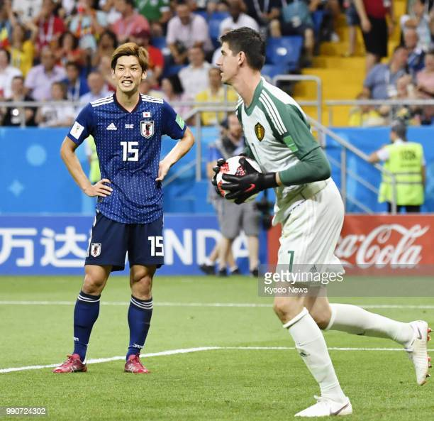 Thibaut Courtois of Belgium holds the ball near Yuya Osako of Japan during the first half of a World Cup roundof16 match in RostovOnDon Russia July 2...