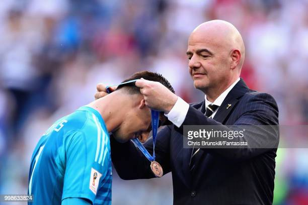 Thibaut Courtois of Belgium is presented with his third place medal by FIFA President Gianni Infantino after the 2018 FIFA World Cup Russia 3rd Place...