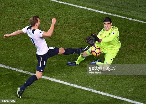 Thibaut Courtois of Chelsea collects the ball while under pressure from Harry Kane of Tottenham Hotspur during the Premier League match between...