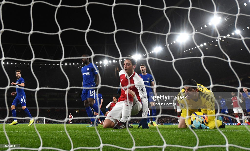 Thibaut Courtois of Chelsea makes a save as Mesut Ozil of Arsenal reacts during the Premier League match between Arsenal and Chelsea at Emirates Stadium on January 3, 2018 in London, England.