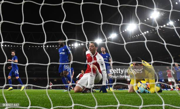 Thibaut Courtois of Chelsea makes a save as Mesut Ozil of Arsenal reacts during the Premier League match between Arsenal and Chelsea at Emirates...